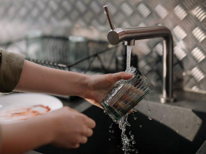 Personne qui fait la vaisselle avec une eau dure