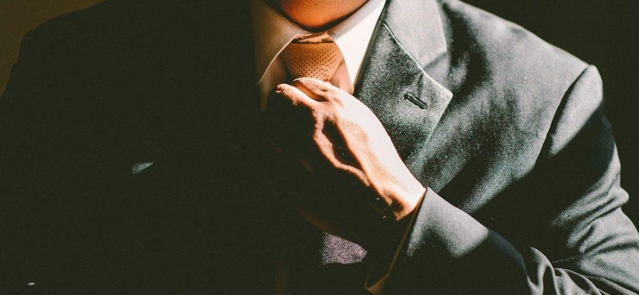 homme qui ajuste sa cravate