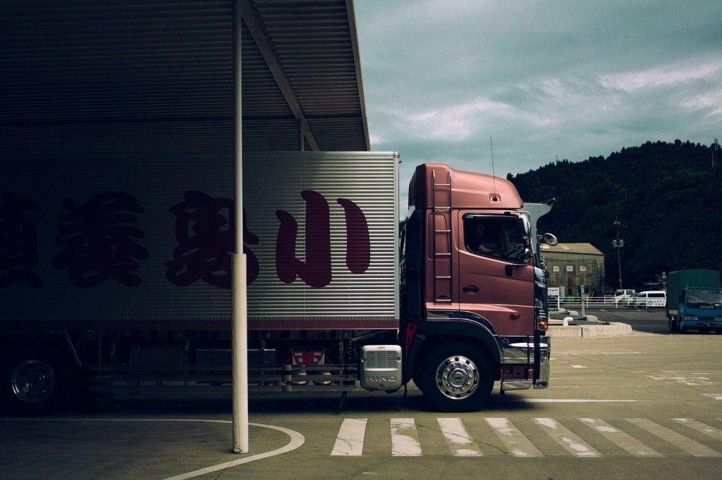 camion de transport quittant un entrepôt