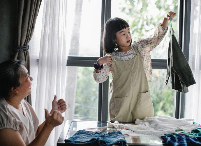 petite fille qui montre un vêtement à sa grand-mère